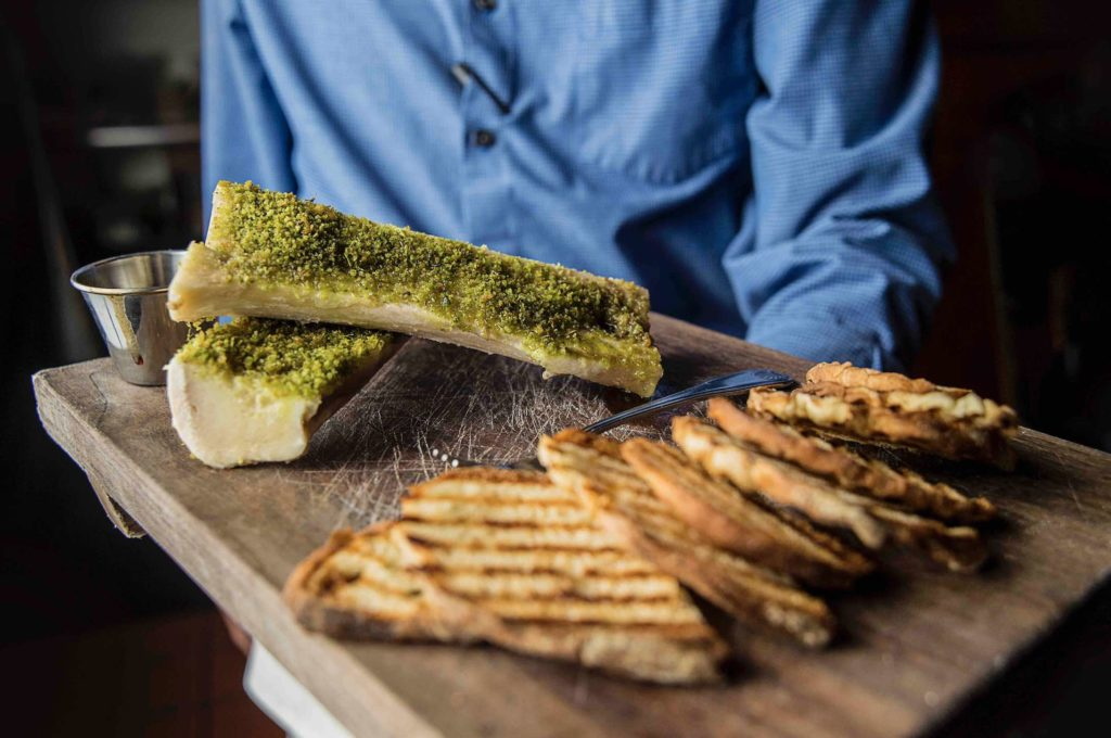 Traditional bone marrow dish with server at Lucky Rooster Kitchen and Bar